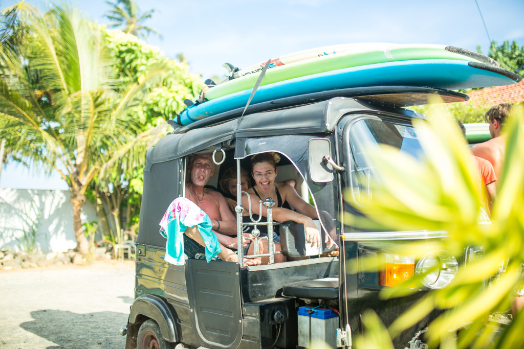 Surfers ready in a tuk tuk, surfboards strapped to the roof, anticipating the afternoon surf